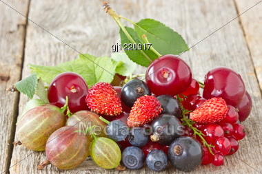 Pile Of Assorted Berries On The Wooden Floor Stock Photo