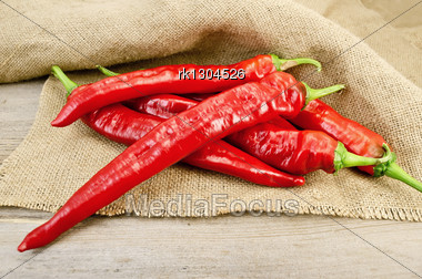 Pile Of Red Pepper On The Background Burlap And Wooden Planks Stock Photo