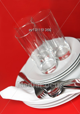 Pile Of White Plates, Glasses With Forks And Spoons On Silk Napkin. Red Background Stock Photo
