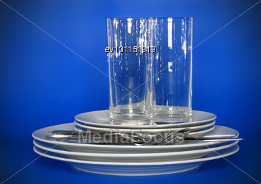 Pile Of White Plates, Glasses With Forks And Spoons On Silk Napkin. Blue Background Stock Photo