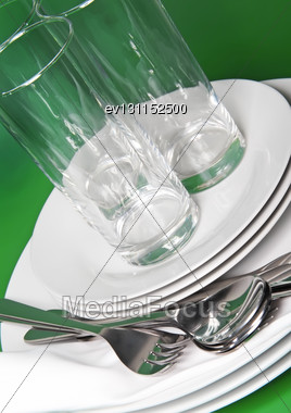 Pile Of White Plates, Glasses With Forks And Spoons On Silk Napkin. Green Background Stock Photo