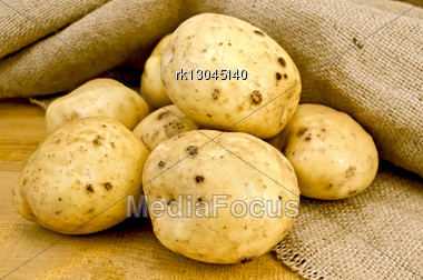 Pile Of Yellow Potato Tubers Against Sacking And Wooden Board Stock Photo