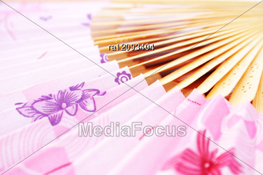 Pink Opened Fan As A Background. Stock Photo
