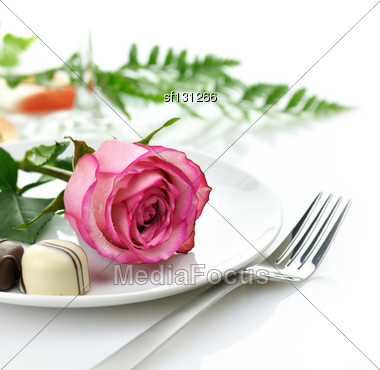 Pink Rose And Chocolate Candy On A White Plate Stock Photo