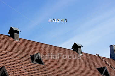 Pipe Of Ventilation And Windows On A Roof Of Tiles Stock Photo
