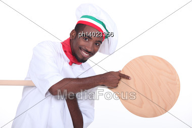 Pizza Maker Pointing To A Pizza Peel Stock Photo