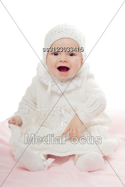 Playful Baby Girl Sitting With Open Mouth. High Key Stock Photo