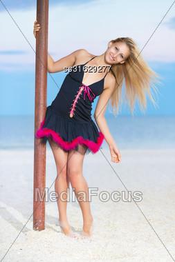 Playful Blond Woman In Black Peignoir Posing On The Beach Stock Photo