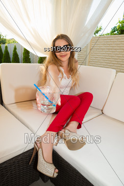 Playful Blond Woman With Cocktail Relaxing Outdoors Stock Photo