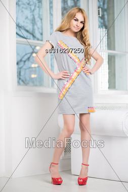 Playful Blond Woman Posing In Short Gray Dress Near The Window Stock Photo