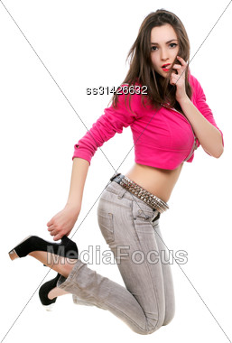Playful Brunette In Short Pink Jacket Holding Her Heel. Isolated On White Stock Photo