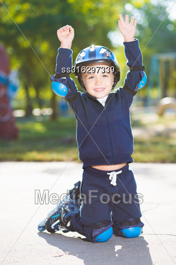 Playful Little Boy Posing On The Knee Pads Stock Photo