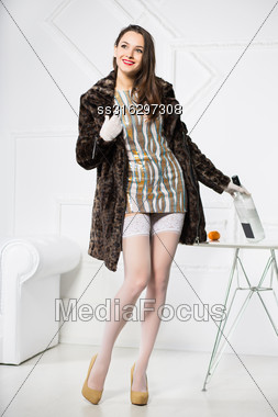 Playful Woman Wearing Short Dress And Fur Coat Posing With Bottle Stock Photo