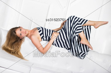 Playful Young Blond Woman Lying On The White Sofa Stock Photo