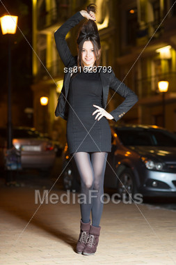 Playful Young Brunette Wearing Black Clothes Posing Near The Road Stock Photo