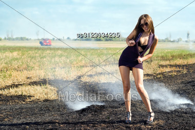 Playful Young Woman In The Burning Field Stock Photo