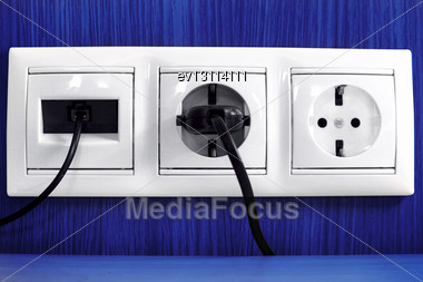 Plugs In Electric And Phone Socket Stock Photo