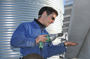 Plumber Attaching Guttering To A Commercial Building Stock Photo