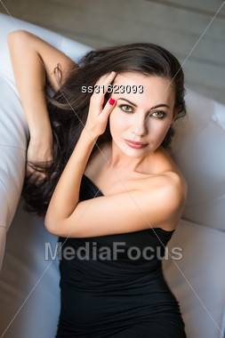 Portrait Of Attractive Brunette Posing On The Couch Stock Photo