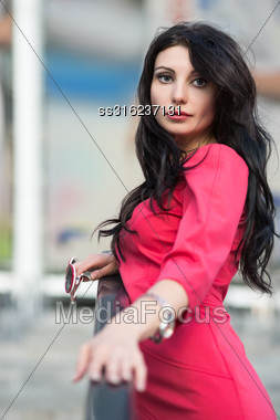 Portrait Of Attractive Brunette In Red Dress Posing Outdoors Stock Photo