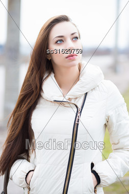 Portrait Of Attractive Brunette In White Jacket Posing Outdoors Stock Photo