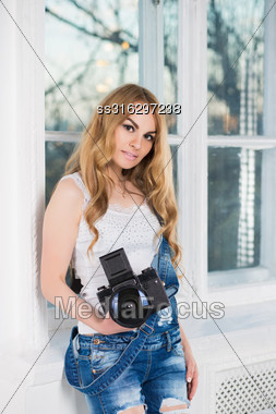 Portrait Of Attractive Woman With Camera Posing Near The Window Stock Photo