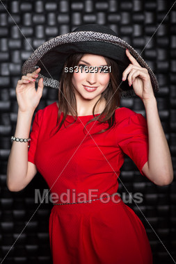Portrait Of Attractive Woman Posing In Red Dress And Hat Stock Photo