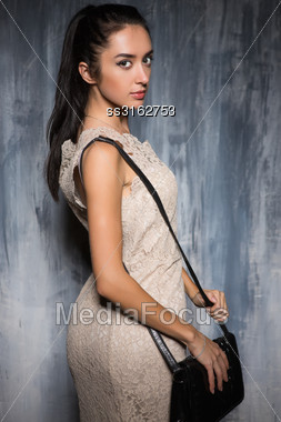 Portrait Of Attractive Young Brunette Posing With Handbag Stock Photo