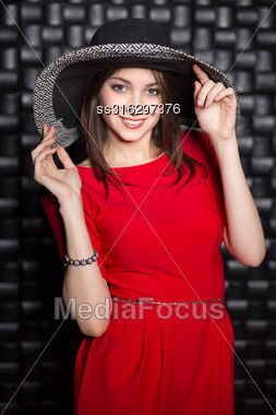 Portrait Of Attractive Young Woman Wearing Red Dress And Hat Stock Photo