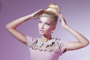 Portrait Of Beautiful Blond Girl In Pink Dress Looking Like Barbie Doll Over Pink Background Stock Photo