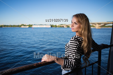 Portrait Of Beautiful Blonde Posing In Striped Blouse Near The River Stock Photo