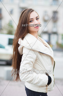 Portrait Of Beautiful Brunette In White Jacket Posing Outdoors Stock Photo