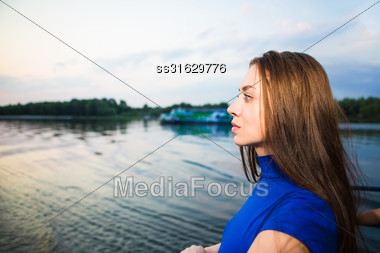 Portrait Of Beautiful Pensive Young Brunette Posing Near The River Stock Photo