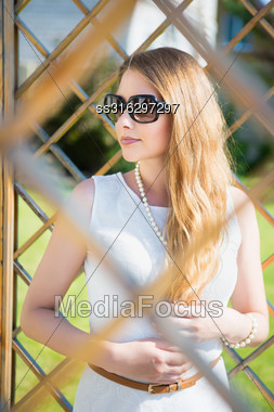 Portrait Of Beautiful Thoughtful Blond Woman In Sunglasses Posing Outdoors Stock Photo