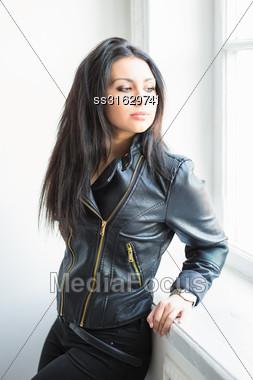 Portrait Of Beautiful Thoughtful Brunette Posing Near The Window Stock Photo
