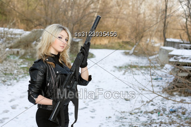 Portrait Of Beautiful Young Blonde With A Gun Outdoors Stock Photo