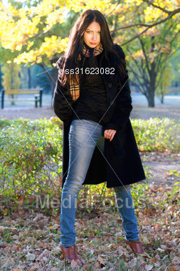 Portrait Of A Beautiful Young Brunette In Autumn Park Stock Photo