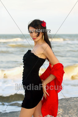 Portrait Of Beautiful Young Brunette In Black Dress On The Beach Stock Photo