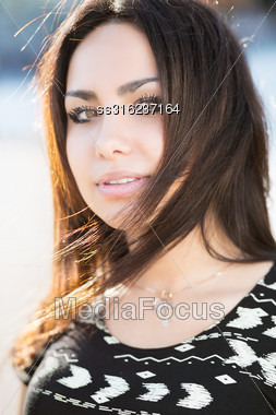 Portrait Of Beautiful Young Brunette Posing Outdoors Stock Photo