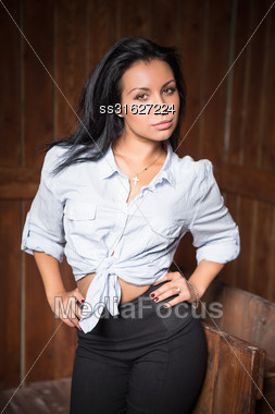 Portrait Of Beautiful Young Brunette Wearing White Shirt And Black Pants Stock Photo