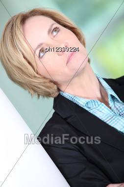 Portrait Of Blond Woman Leaning Against Wall Stock Photo