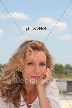 Portrait Of Blond Woman Outdoors On A Sunny Day Stock Photo