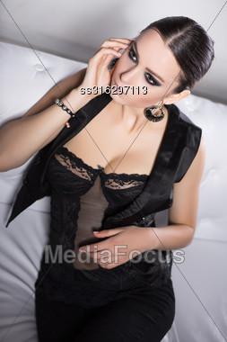 Portrait Of A Brunette In Black Lingerie And Vest Posing On White Sofa Stock Photo