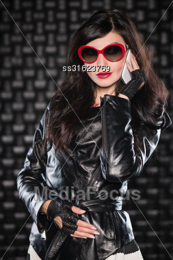 Portrait Of Charming Brunette In Black Leather Jacket And Red Sunglasses Talking On The Phone Stock Photo