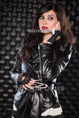 Portrait Of Charming Brunette Wearing Black Leather Jacket And Talking On The Phone Stock Photo