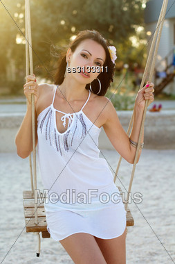 Portrait Of Charming Young Brunette Sitting On A Swing Stock Photo