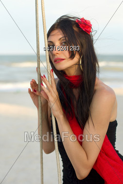 Portrait Of Charming Young Woman Sitting On A Swing Stock Photo