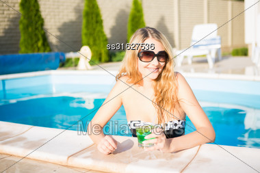 Portrait Of Cheerful Blond Woman Posing In The Swimming Pool Stock Photo