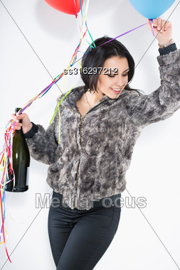 Portrait Of Cheerful Brunette With A Big Bottle And Balloons Wearing Furry Jacket Stock Photo