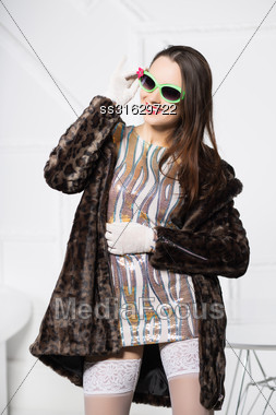 Portrait Of Cheerful Brunette Wearing Fur Coat And Funny Glasses Stock Photo